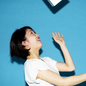頭上に飛んでいるオブジェを見る女性の横顔。驚いたような楽しげな表情。ライトブルーの背景。