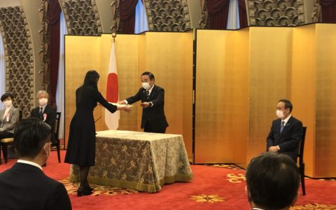坂本内閣府特命担当大臣に表彰状を授与される代表の山上
